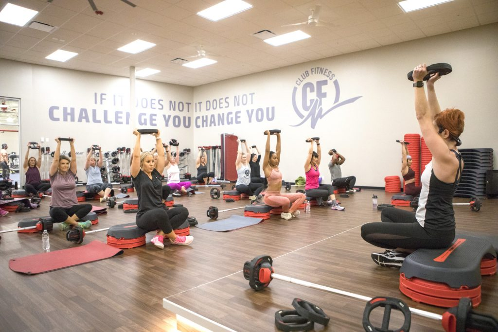 A group of women in workout class lift weights above their heads.
