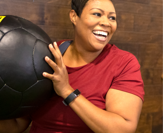 Member Shaniece T. of Club Fitness Maplewood works out with a medicine ball