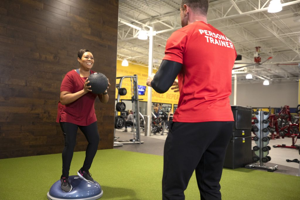 A Club Fitness member works out with a medicine ball and personal trainer