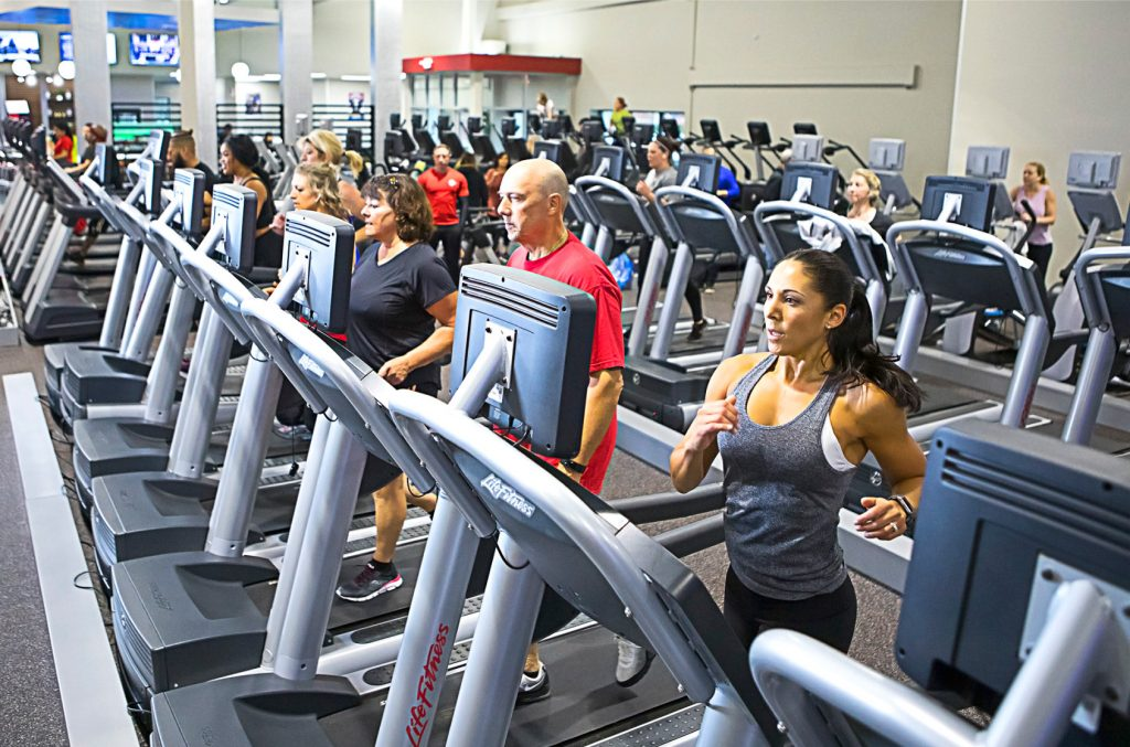 Club Fitness members walk and run on treadmills